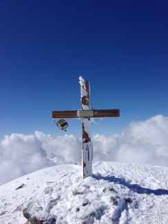 Wooden cross on a snowy mountaintop