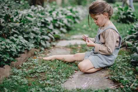 Child playing with chalk outside