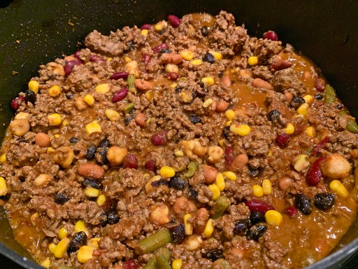 Ground beef with tomatoes beans, and veggies cooking in a chili pot