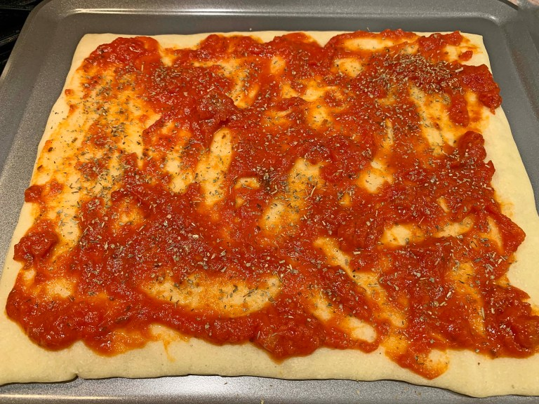 Red pizza sauce and Italian seasoning on pizza dough