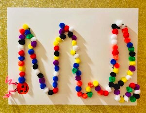 Colorful pom pom balls forming the initials of a name on a white piece of paper