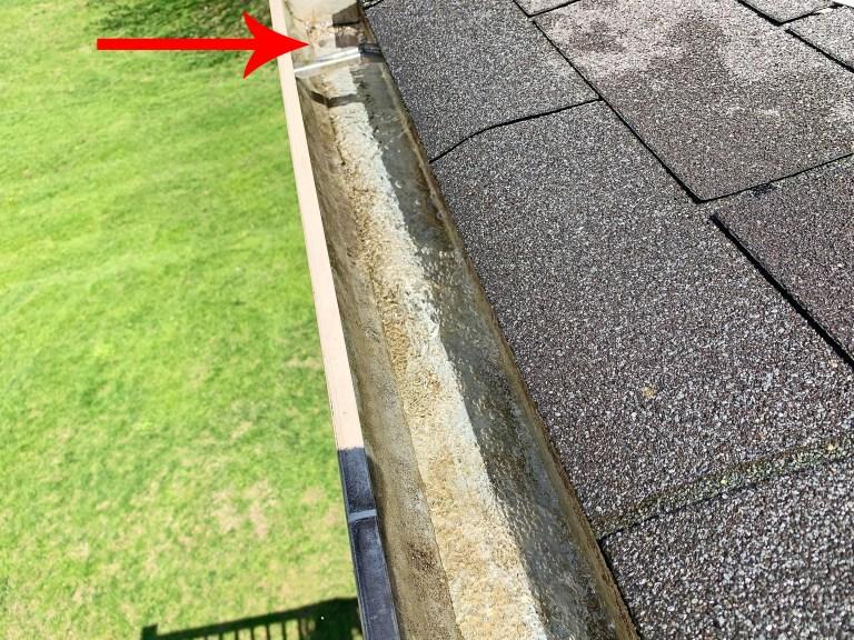 Hose water flushing debris from a gutter toward a gutter downspout