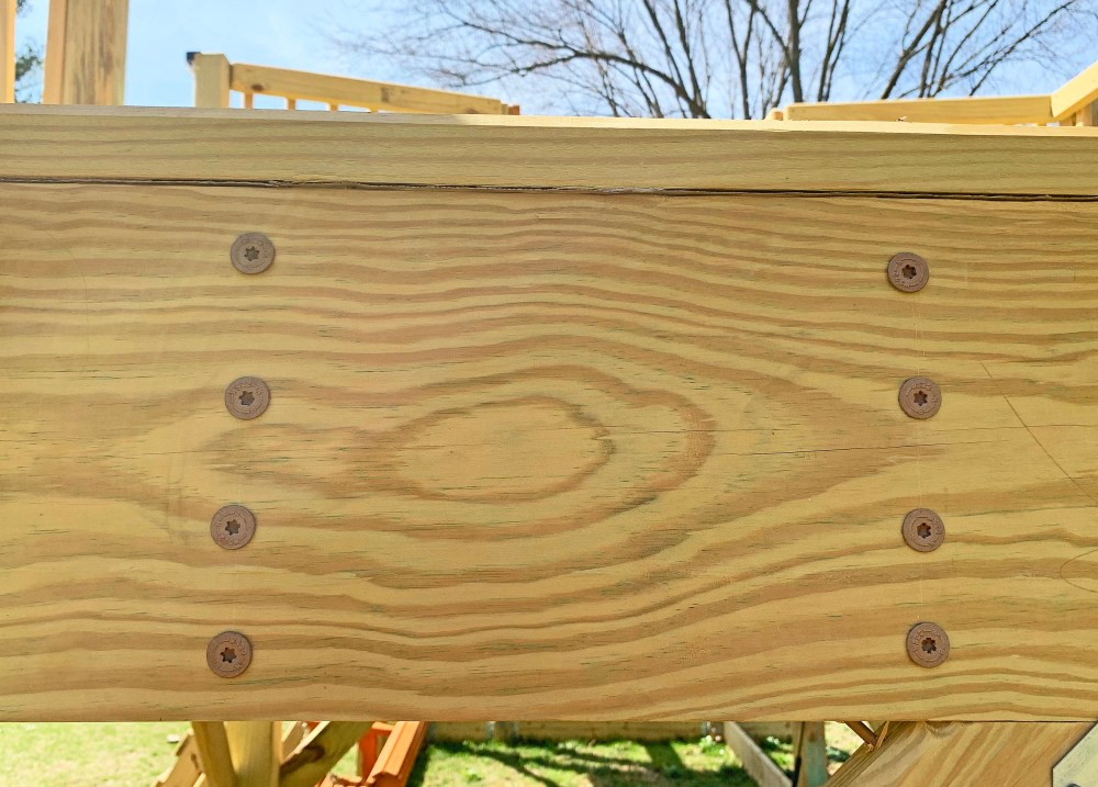Four 8 inch timber screws securing a joist to double 2x support beams on the actual playground