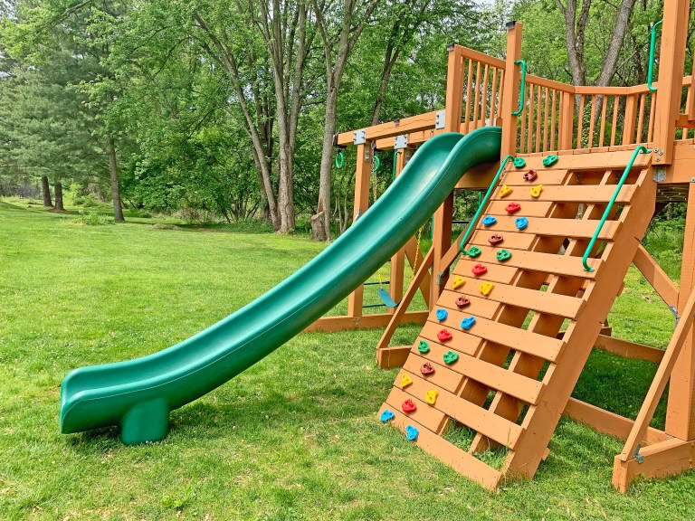 Long green slide attached to a playground