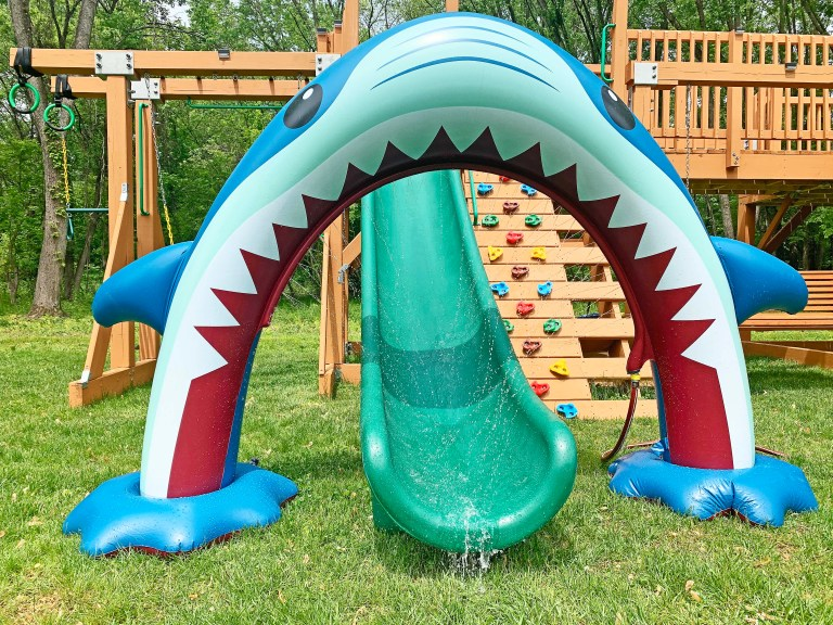Sprinkler in the shape of a giant shark's mouth, spanning over a slide on a playground