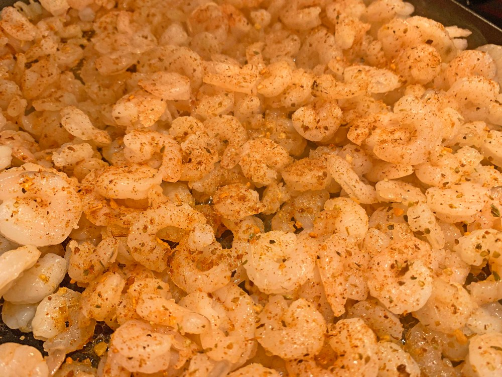 Pinkish-white colored shrimp with beige-colored seasoning in a black frying pan