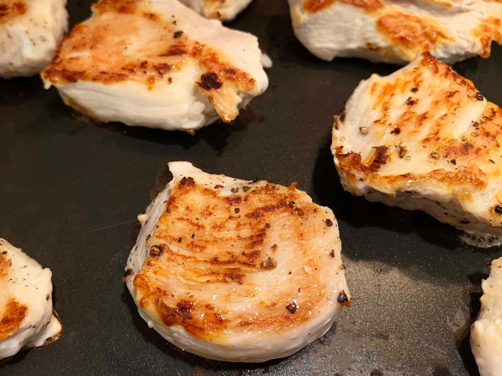 Cooked chicken breasts in a black frying pan