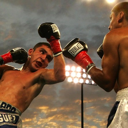 Two boxers squaring off beneath an open sky