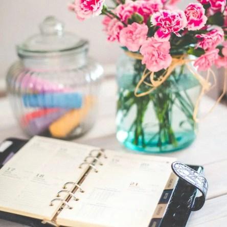 An open planner beside a bouquet of pink flowers
