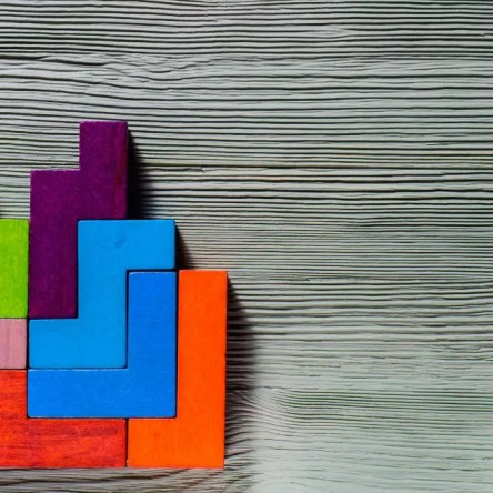 Brightly coloured geometric blocks on a wooden background