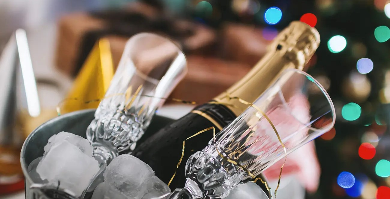 A bottle of champagne in an ice bucket, against a background of sparkling lights