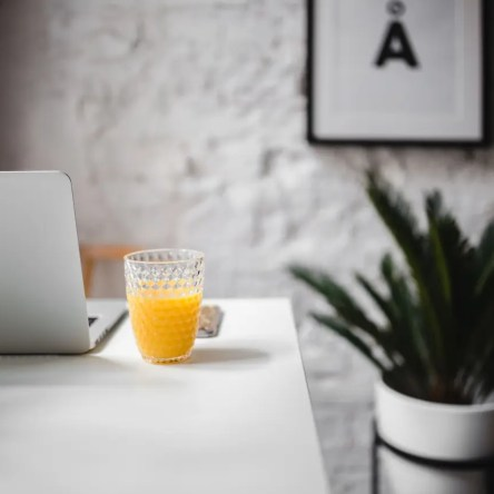A laptop and a glass of orange juice on a white desk