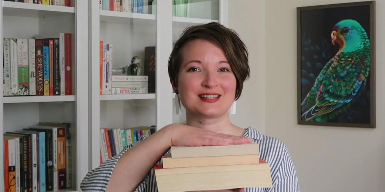 Christina smiles, while holding up three books