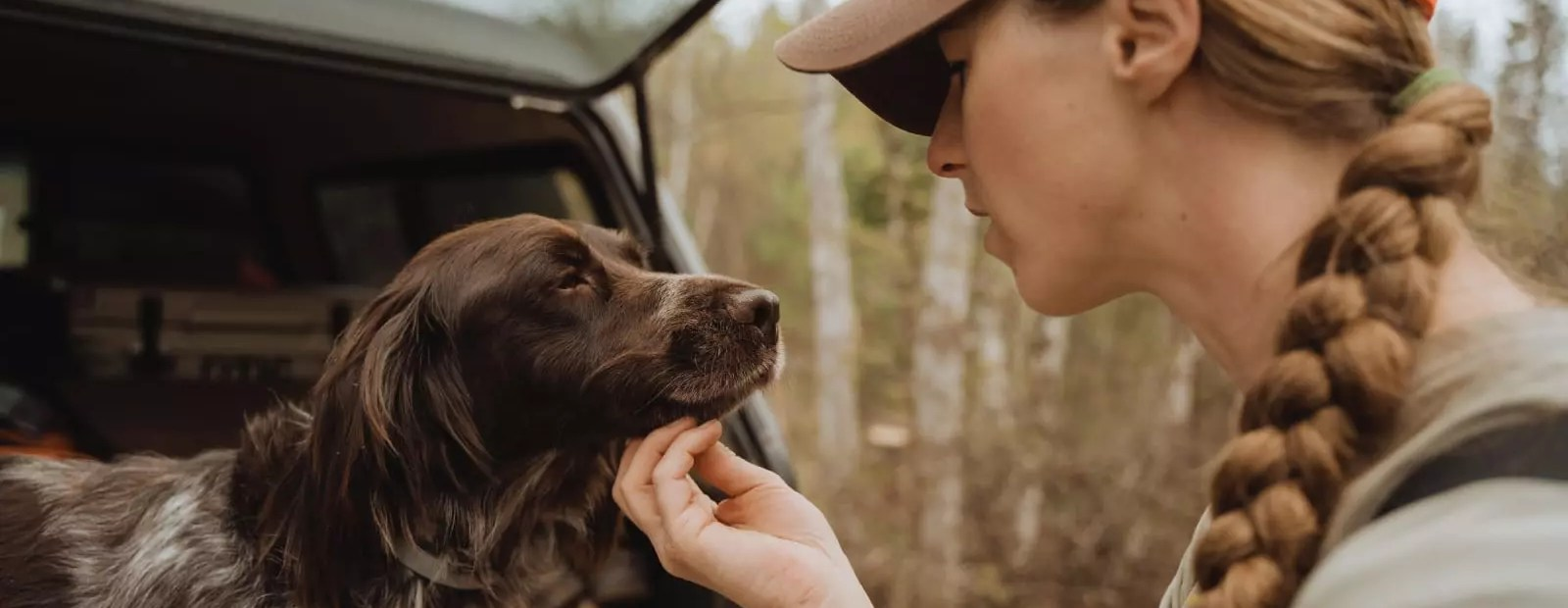 A woman looks at a bird dog.