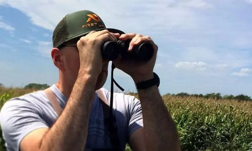 A dove hunter uses binoculars to scout dove fields.