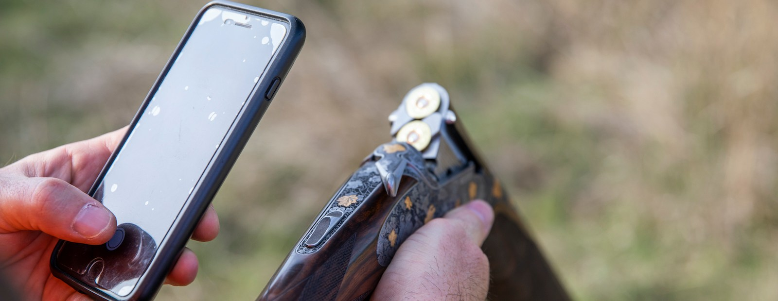 A hunter uses a cell phone while holding an over-under shotgun