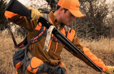 A bird hunter uses a bore snake to clean his shotgun