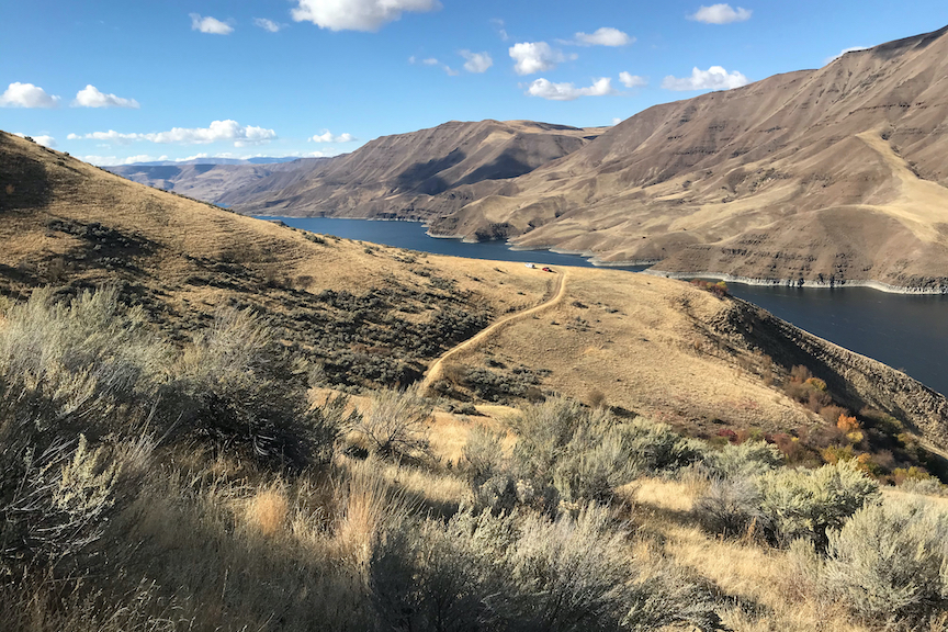 Landscape photo of Hells Canyon with two trucks in the distance