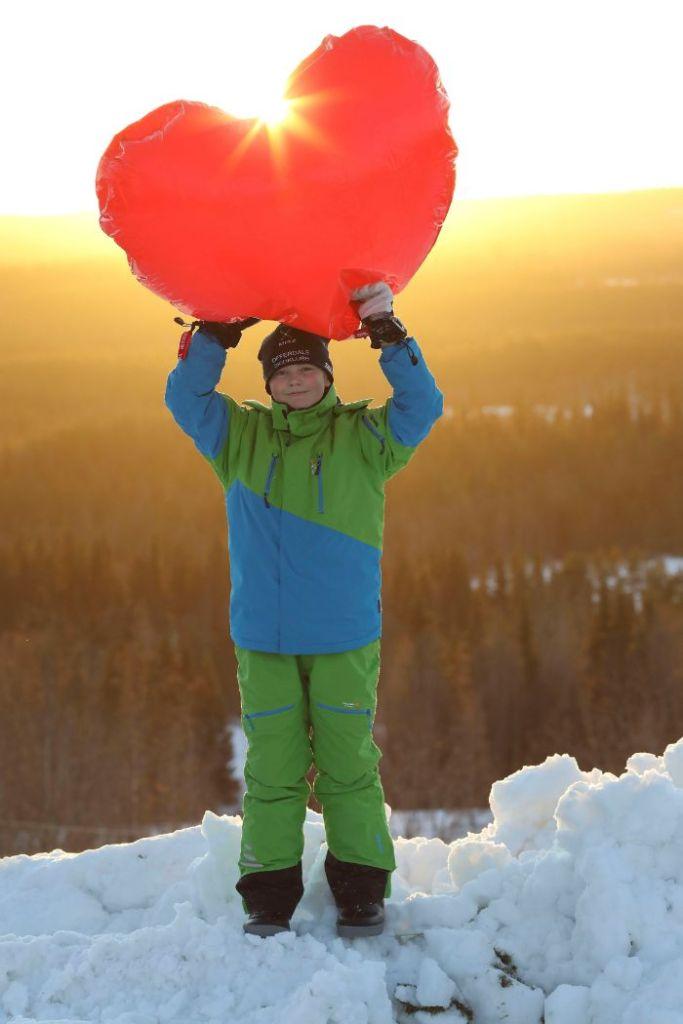 Ett barn håller ett stort plasthjärta ovanför huvudet, solen strilar igenom