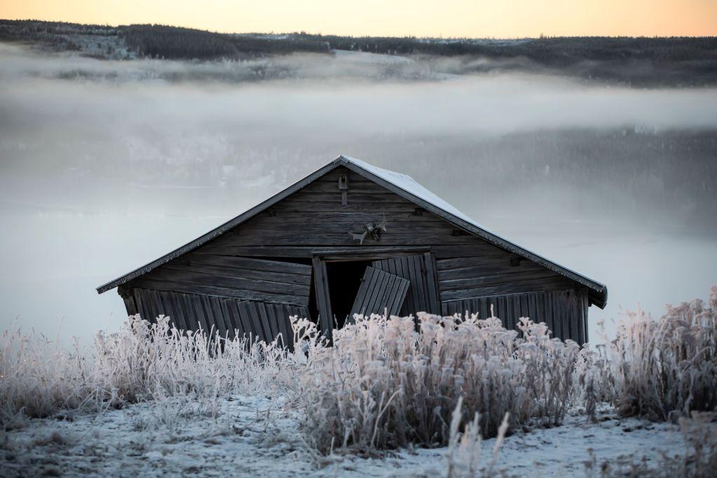 En fallfärdig lada i morgonljus med frost
