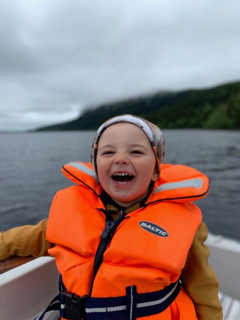Liten pojke i fiskebåt på en sjö