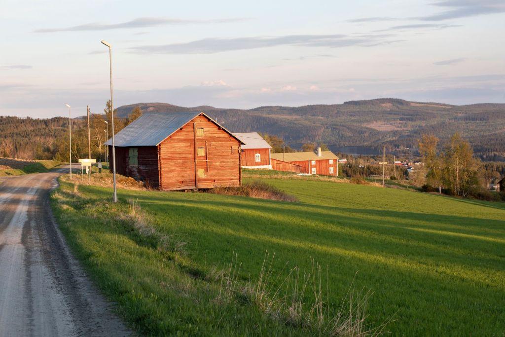 Lador och hus vid en grusväg