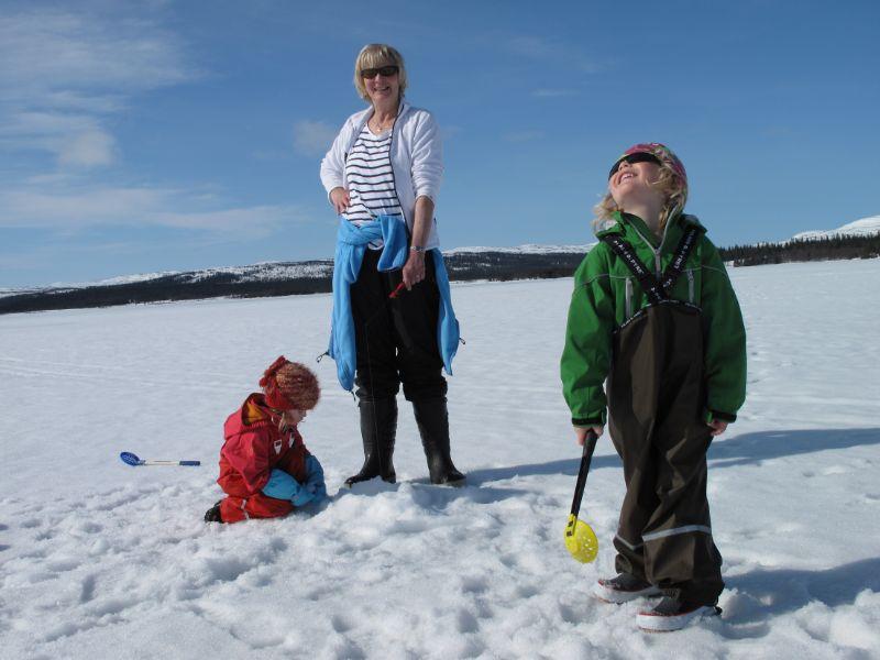 Två barn som sitter på isen, en vuxen som pimplar
