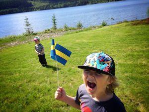Två barn som viftar med svenska flaggan under nationaldagen
