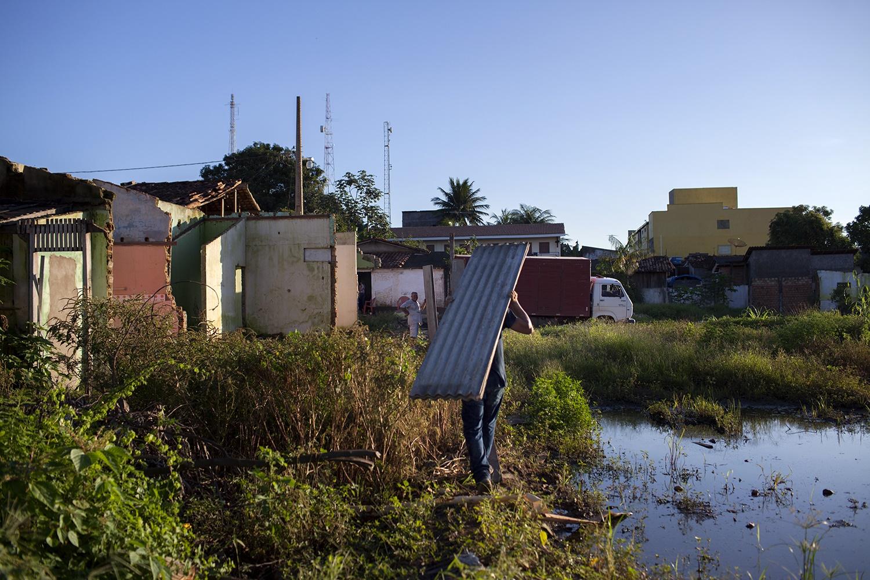 """Alex Soares, 47 anos, nascido e criado em Altamira. Na foto ele retira algumas telhas que guardou de sua casa que foi demolida: """"Eu tinha uma casa boa. Fui esmagado por um rolo compressor. Não tive escolha. Ou aceitava ou ficava sem nada"""""""