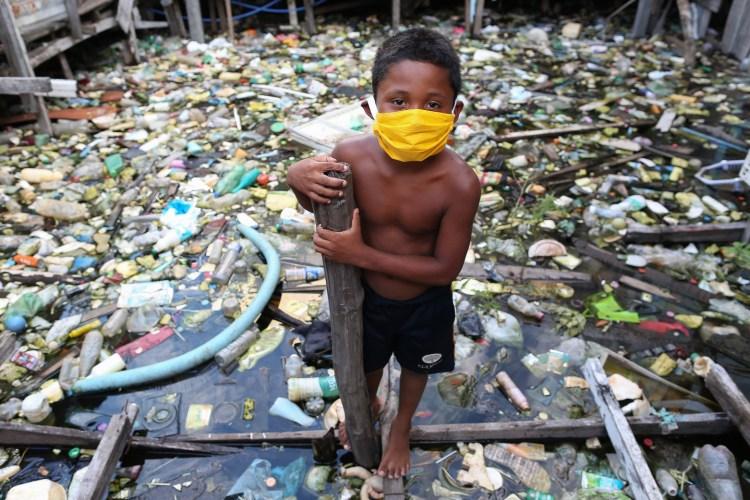 Um menino da comunidade ribeirinha de Educandos, em Manaus, brinca em meio ao lixo. Foto Michael Dantas/AFP