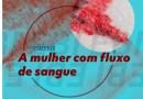 """Ao fundo, uma mancha de sangue. Na frente, sobre um filtro azul, os escritos """"A mulher com fluxo de sangue"""". No lado inferior direito, a logo do projeto redomas."""
