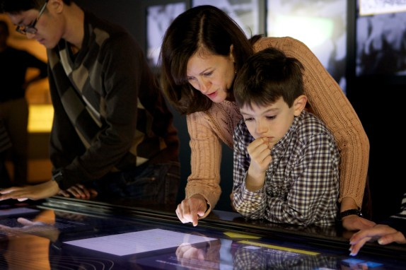 Curator Alice Kamps shows her son how to use the touchscreen on the interactive table.