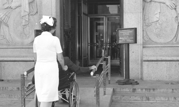 A nurse pushes a person in a wheelchair up the ramp at the entrance on the Pennsylvania Avenue side of the National Archives Building, c. 1969. (Records of the National Archives)