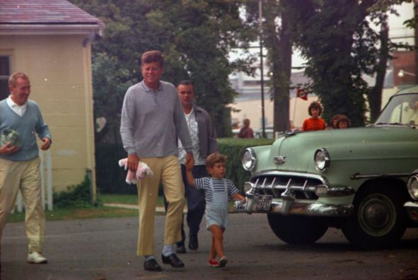 """President John F. Kennedy and John F. Kennedy, Jr., depart a candy store in Hyannis Port, Massachusetts, during Labor Day Weekend. Under Secretary of the Navy, Paul B. """"Red"""" Fay, walks at left; White House Secret Service agent, Hank Rybka, walks behind President Kennedy."""