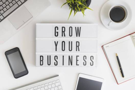 A piece of paper saying Grow Your Business, next to it is a mobile phone and a computer. Learn how to select your eyelashes suppliers with me.