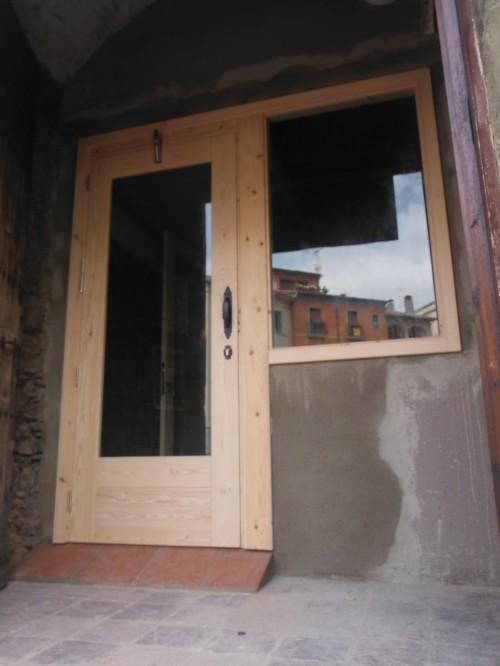 Promida porta entrada local amb finestra