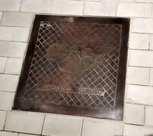 Carlos Garaicoa,Sin título (Alcantarillas), 2014 Instalación. Cinco bajo relieves en bronce, madera, adoquines, proyección de fotos fijas Dimensiones variables