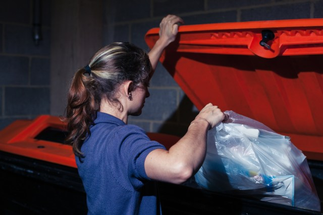 Woman putting trash in bin at an apartment community that does not have valet trash service