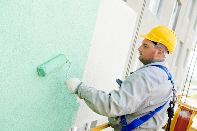 Man Painting Exterior Apartment Building Walls With Roller Brush Hiring Apartment Painting Contractors