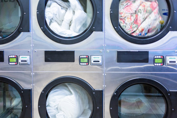 Industrial Washing Machines In Multifamily Laundry Room Controlled with Laundry Mobile Apps On Smartphones
