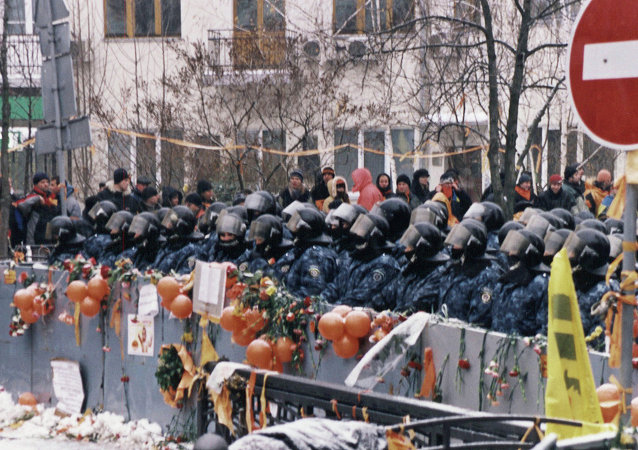 Color photograph of scene in Kiev street. Police in riot gear standing behind barricade which is festooned with orange balloons. Building in background