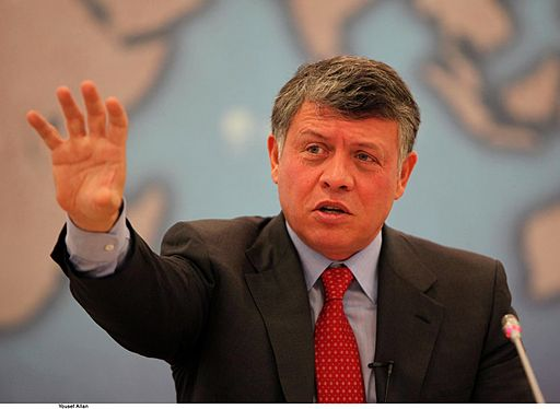 Is Israel Worried About Saudi Arms Deal? Colored photograph of King Abdullah II of Jordan, wearing a dark suit and red tie. He has a serious face, slightly open mouth and is raising his right hand.and