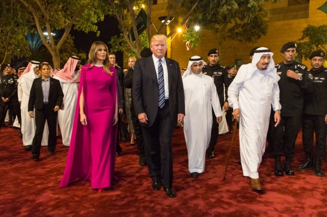 Is Israel Worried About Saudi Arms Deal? A colored photograph of President Trump and Melania Trump, wearing a long magenta dress with cape, and Saudi King and other officials wearing white robes .
