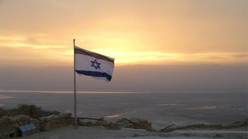 Colored photograph of Israeli flag flying on hilltop at sunset. God's Final Warning.