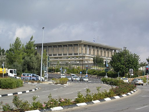 "Colored photograph of the rather square and flat roofed Israeli Knesset building with an approach road divided by a black and white median strip planted with bushes. ""Burdensome stone"""
