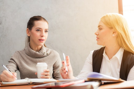 Colored photograph of a young woman with a turtle neck jumper talking with another young woman in white blouse and black vest. Both seated at a table with books and pens on it. Fiery torch in the sheaves