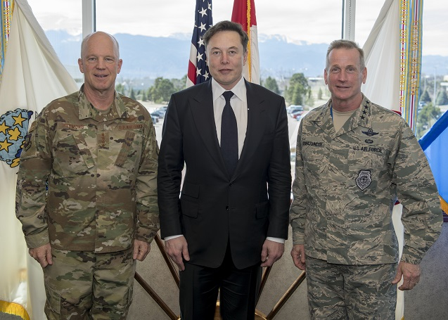 Colored photograph of a man in a black suit flanked by 2 U.S. airforce officers wearing camouflage uniforms. Large windows, flags on stands and hills in background. Beast Interface.e off