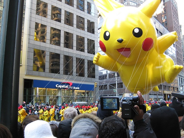 Huge inflated yellow Pikachu balloon held above a crowd. Tall building with many windows in background. Better than Pokemon.