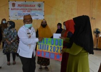 Bupati Gorut, Indra Yasin, saat menyerahkan BLT. Jum'at, (15/01/2021). (Foto : Humas).