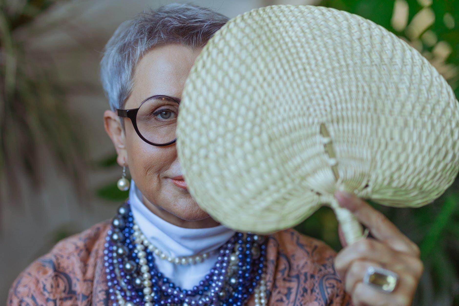 photo of woman holding a fan